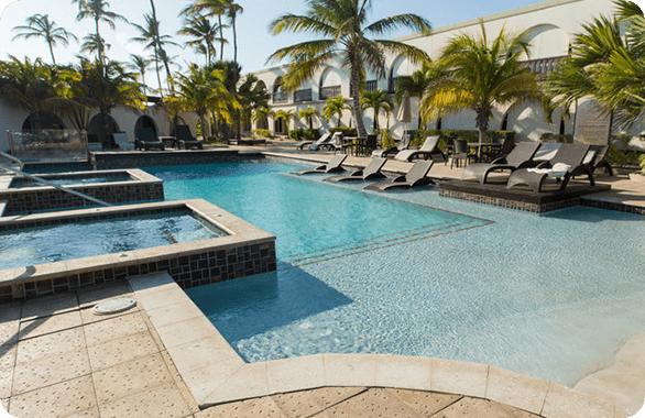 Large pool surrounded by palm trees located at the Talk of the Town Hotel & Beach Club in Oranjestad, Aruba.